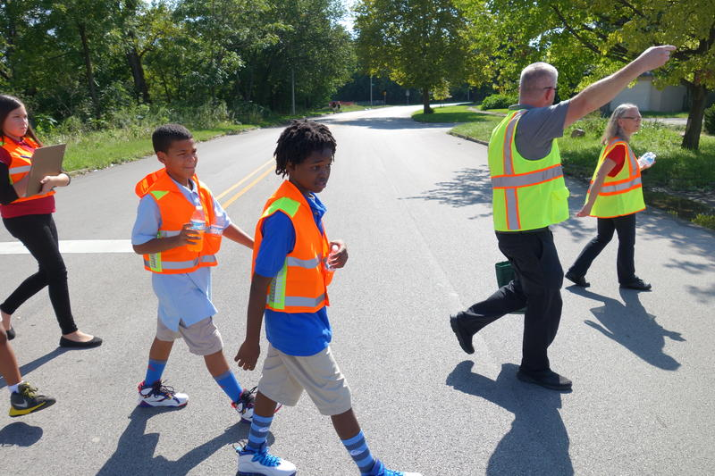 Allan Henderson, second from right, who manages Safe Routes to SChool programs with the non-profit Health By Design, leads a group of students on a walk audit.