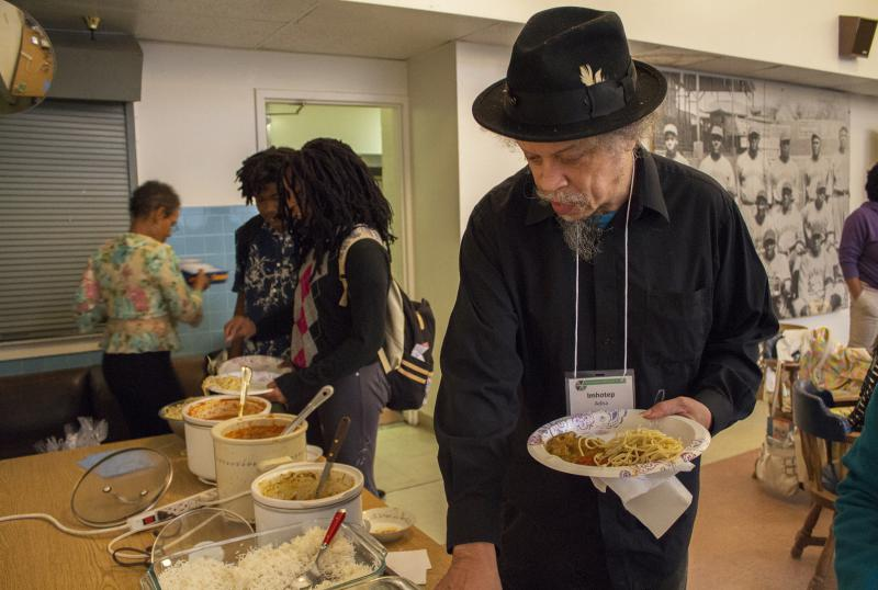 Imhotep Adisa, Executive Director of the Kheprw Institute, samples the homemade buffet at the group's monthly reception.