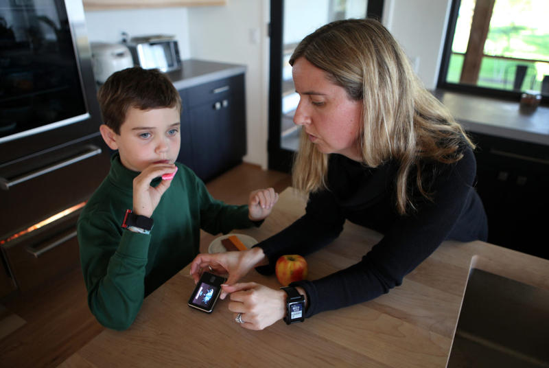 Jack Christensen, 8, has an after-school snack at his home in Waunakee, Wis. His mother, Jess Franz-Christensen, logs his carbohydrate intake on a monitoring device. Jack has Type 1 diabetes.