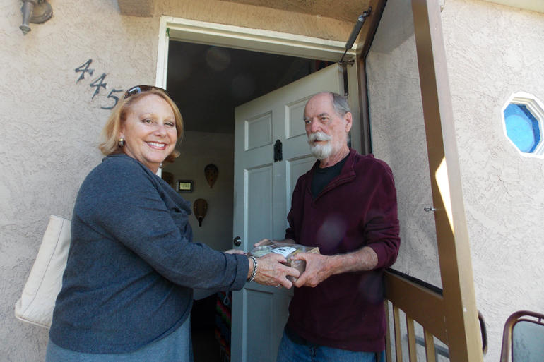 Debbie Case, CEO of the Meals on Wheels San Diego County, delivers lunch and dinner to 75-year-old Dave Kelly. Kelly lost his sight about two years ago and reluctantly gave up cooking.