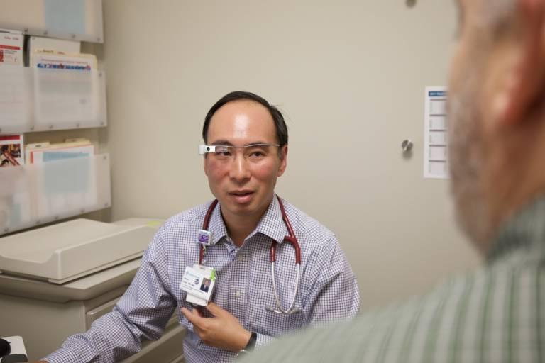 During patient exams, Dr. Albert Chan wears Google Glass, which transmits a feed to a note-taing offsite medical scribe so Chan can better focus on the patient.