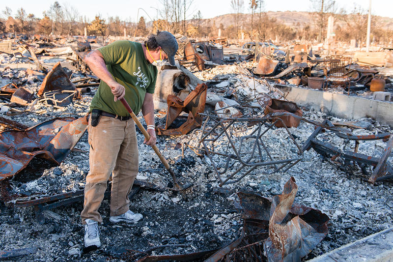 Ed Corn wears a mask as he sifts through the ashes of the home he shared with his paraplegic roommate in Santa Rosa's Coffey Park neighborhood.