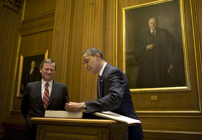 John Roberts looks on as Present-Elect Barack Obama signs the guest book at the U.S. Supreme Court in 2009.