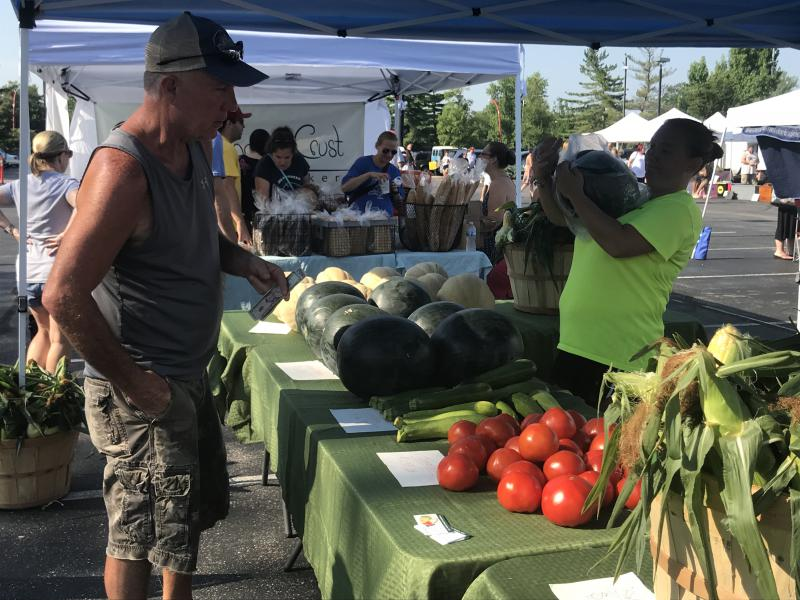 Samantha Wilmot bags a watermelon for a customer at the Columbus Farmers Market in Barthlomew County. Wilmot is one of many farmers market vendors who accepts Supplemental Nutrition Assistance Program benefits.