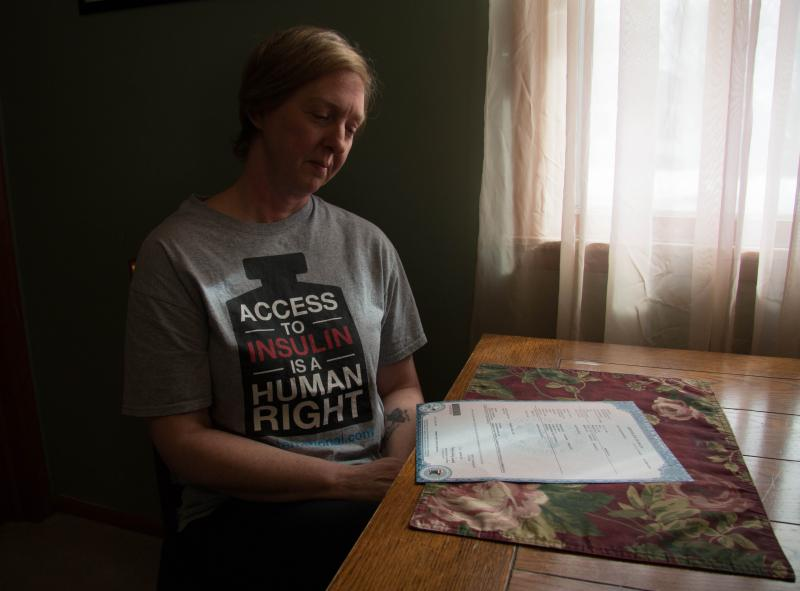 Nicole Smith-Holt looks at her son Alec's death certificate in her Richfield, Minn. home. Alec died in 2017 from diabetic ketoacidosis.