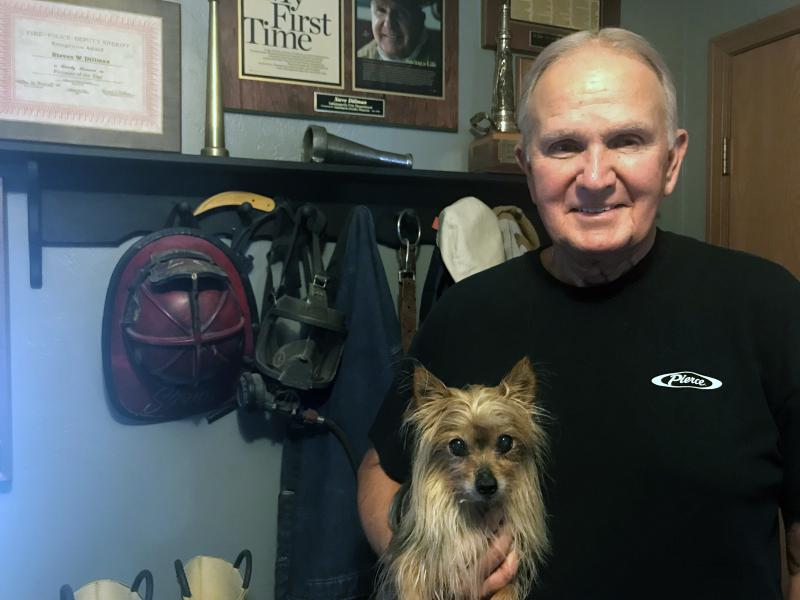 Steve Dillman, holding his 11-year-old yorkie Colt, stands in front of some of his old firefighting gear. The 74-year-old spent 38 years as an Indianapolis firefighter, and was diagnosed with prostate and throat cancers, most likely due to his profession.