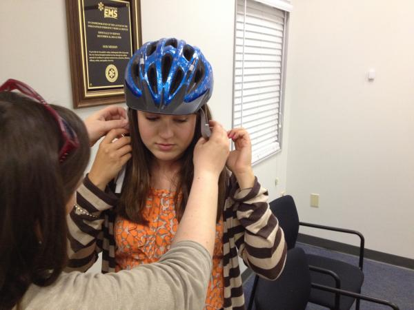 Dr. Weinstein placing a bike helmet on Natalie Moya's head to check for proper fit