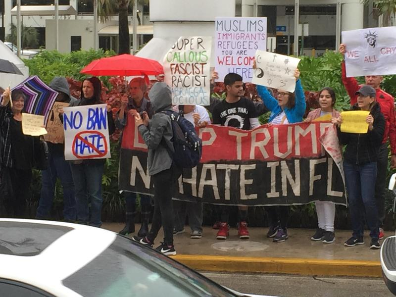 Demonstrators outside Miami International Airport Sunday protesting President Trump's immigration executive order.