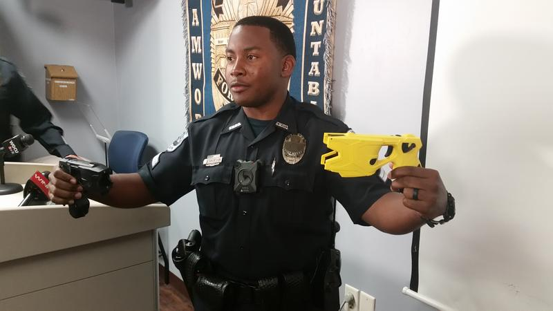 FMPD Officer Jason Jackson demonstrates the difference between the department's old and new tasers