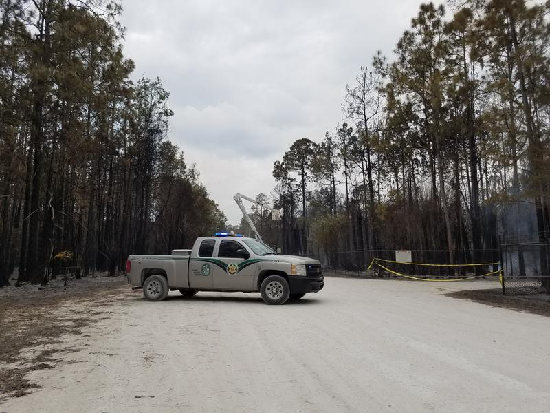 A Florida Fish and Wildlife Conservation truck blocks a roadway boarderd by smoldering trees
