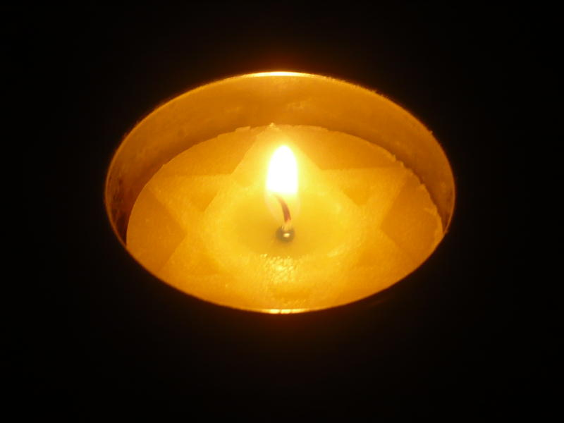 A lit Yom Hashoah candle in a dark room.
