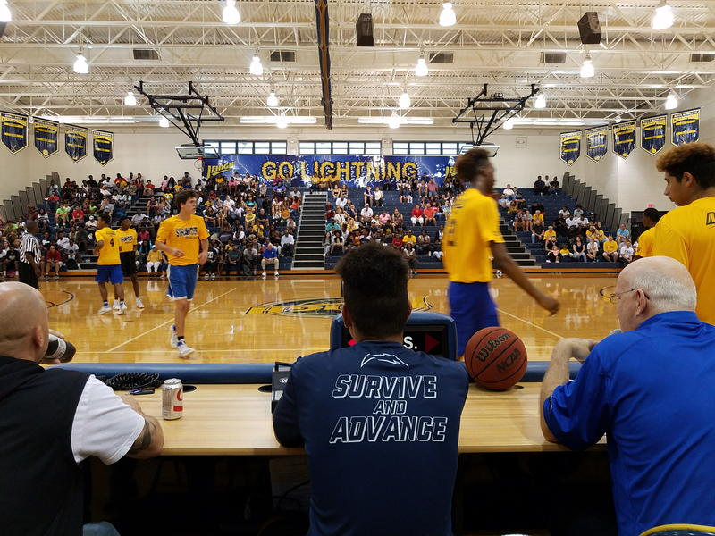 "In the foreground, a man wearing a ""Survive And Advance"" t-shirt  is sitting courtside. In front of him, various basketball players are on the court and in the background are bleachers of spectatos with a ""Go Lightning"" banner hanging overhead."