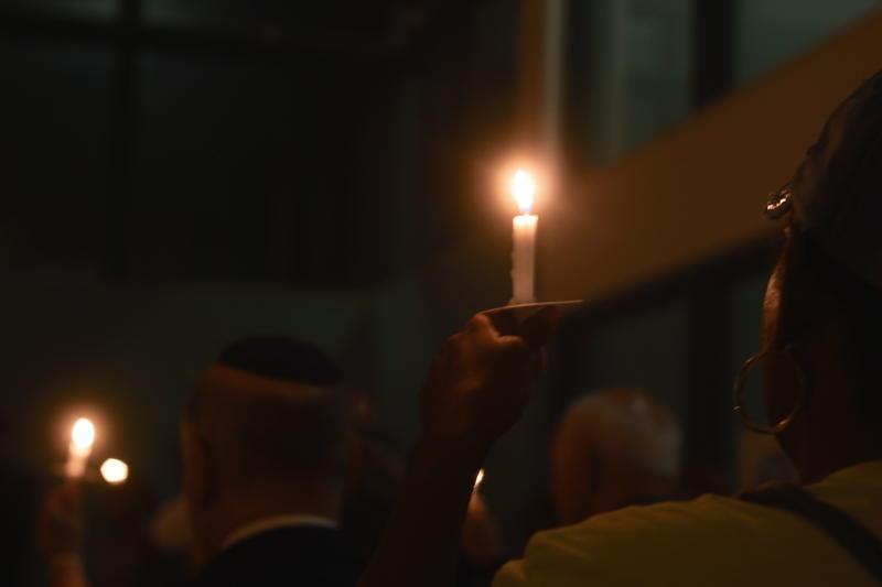 People hold candles during a moment of silence held at the vigil at the Unitarian Universalist Congregation of Naples. There were 250 candles available and not everyone got one.