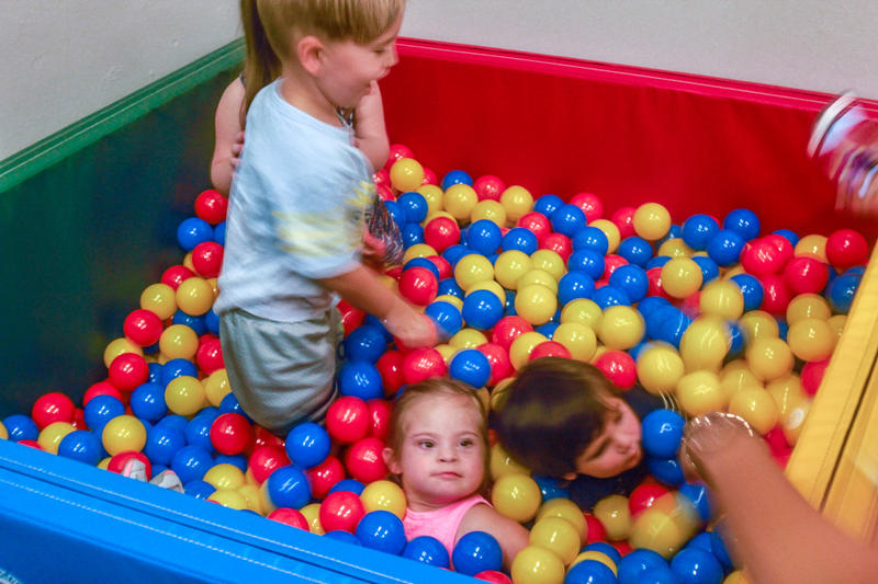 Kids play in a small ball pit at Gigi's Playhouse during the grand opening.