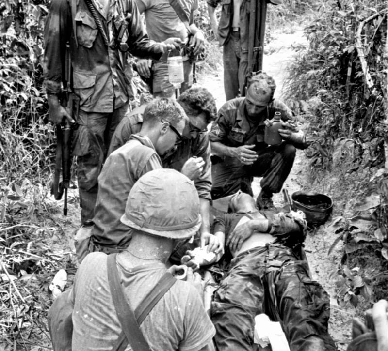 Medics Gerald Snyder and Dennis Ortman of the 2-27th Infantry treat a wounded soldier during a combat operation in the Boi Loi Woods.