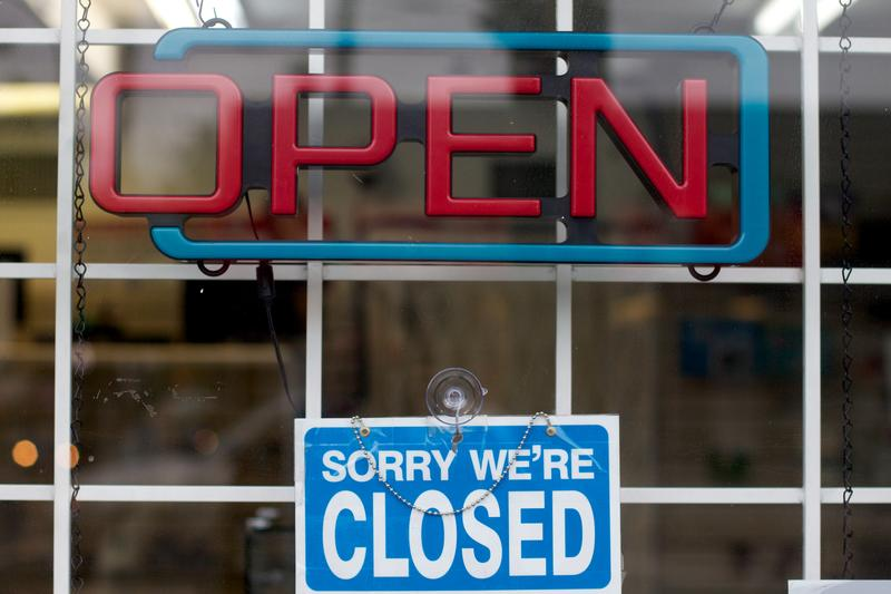 "A ""sorry we're closed"" sign hangs in a window below an off neon open sign"