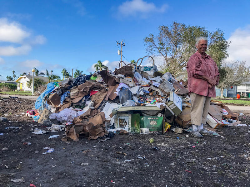 Judy Barton, a 49-year resident of Everglades City, stands in front of a pile of debris she hauled by herself. She's a widow and lives alone, but she had to take a break from the labor because her toe got a bacterial infection from Hurricane Irma cleanup.