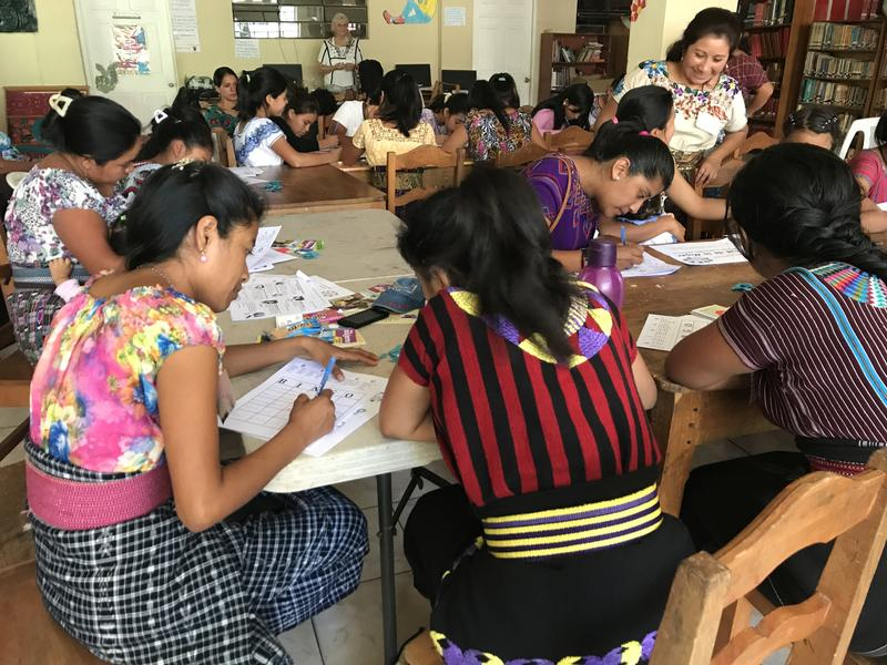 Vilma Morales Hernandez, former student and now teacher, facilitating the reproductive words bingo game in the public library of San Juan La Laguna.