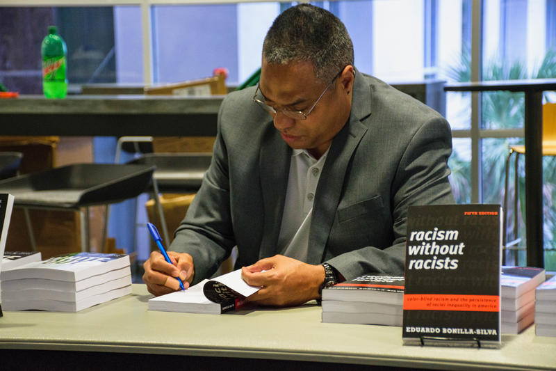 "Dr. Eduardo Bonilla-Silva signs copies of his book ""Racism Without Racists"" before his talk at Florida Gulf Coast University."