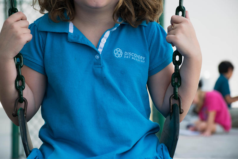 Girl on swing in Discovery Day Academy uniform