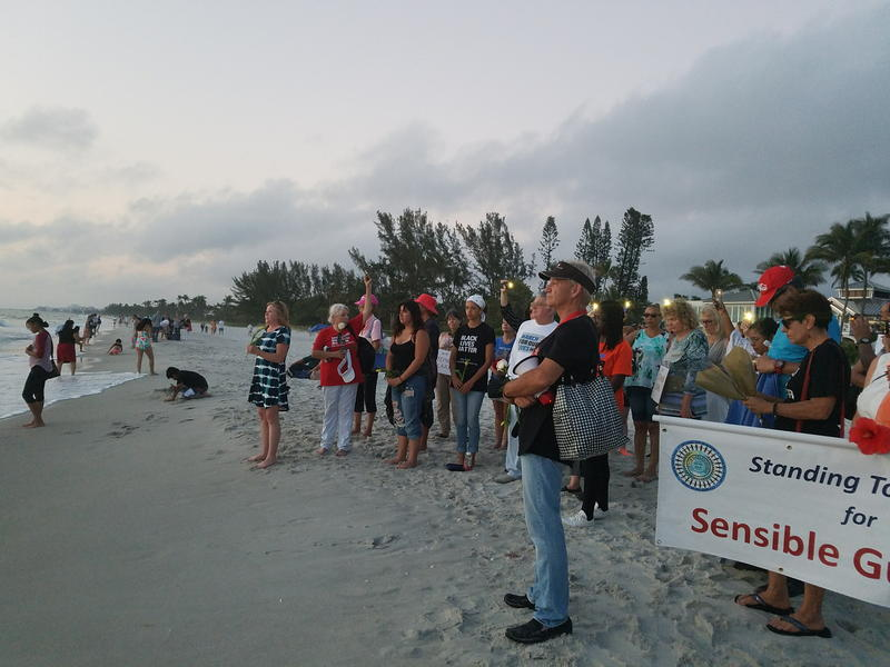 Vigil-goers gathered at the water's edge next to the Naples Pier to have a moment of silence for Stephon Clark and other unarmed black men killed by police.