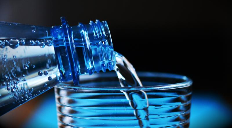Closeup of bottle pouring water into glass