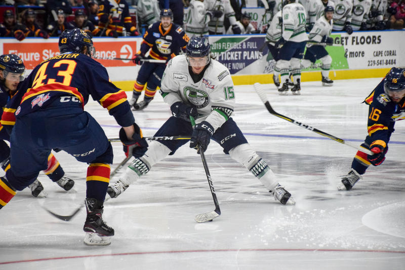 Florida Everblades forward Mitchell Heard tries to keep the puck from the Colorado Eagles surrounding him.