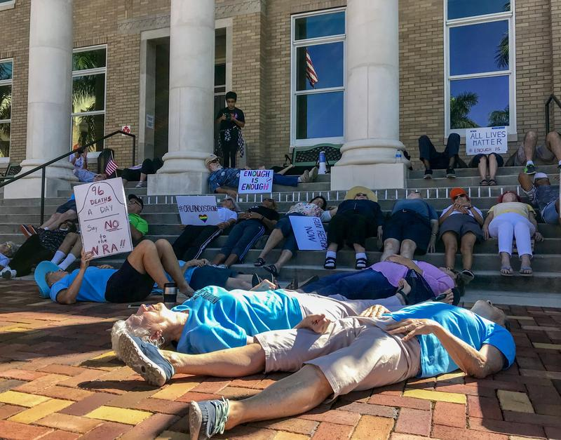 Participants of the die-in lay in front of U.S. Rep. Thomas Rooney's Punta Gorda office in mock-death on the second anniversary of the mass shooting at Pulse nightclub in Orlando.