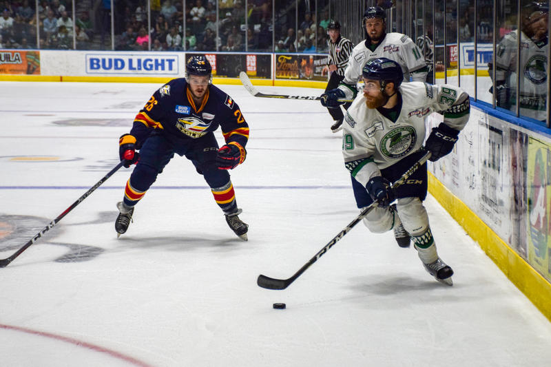 Everblades forward Joe Cox looks to pass the puck away from the Eagles player closing in.