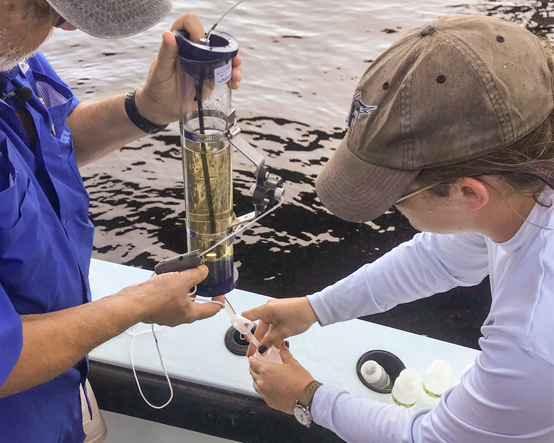Dr. Bill Mitsch and Ph.D. student Lauren Griffiths take a water sample from the Caloosahatchee River to determine where the nitrogen in the water originated.