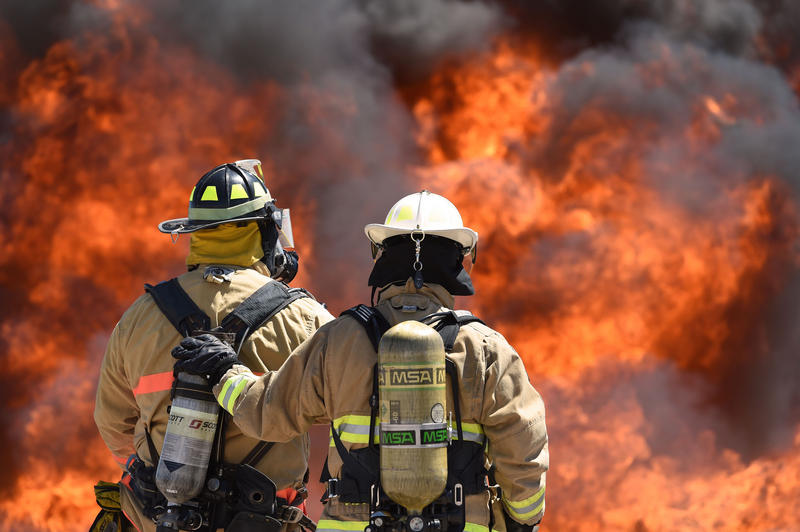 Two firefighters stand in front of a blaze