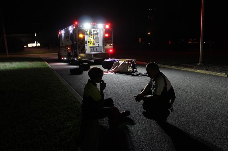 A first responder speaks to someone sitting on a street curb outside a parked ambulance