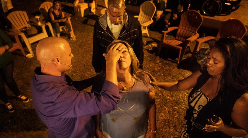 Craig Hunt and his wife Sheanna Hunt pray over Recovering Lives sober home resident Julie Kovach during a service at the home.