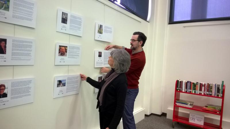 Kathleen Lonbom, co-chair of the Milner Library exhibits program committee, and Ross Griffiths put finishing touches on a display honoring LGBT alumni, faculty and staff from Illinois State University