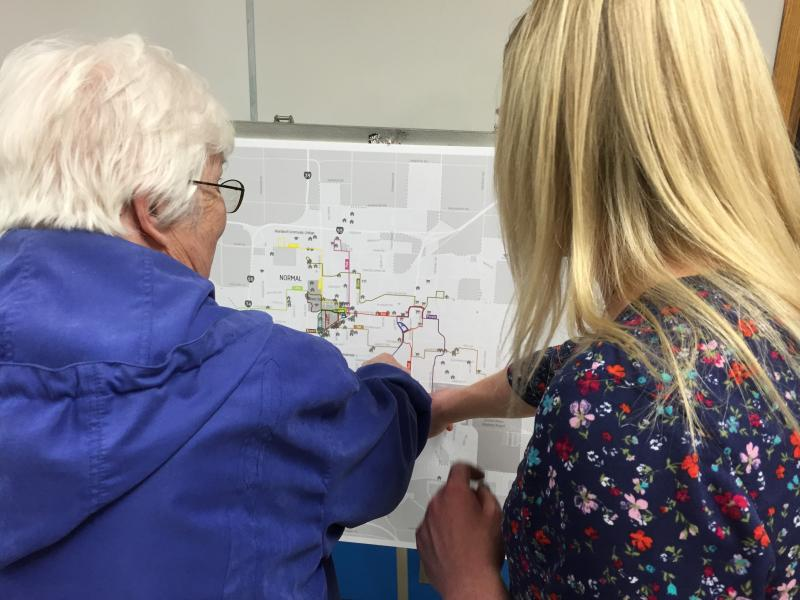 Connect Transit's Melissa Chrisman (right) points out bus route changes to a transit rider