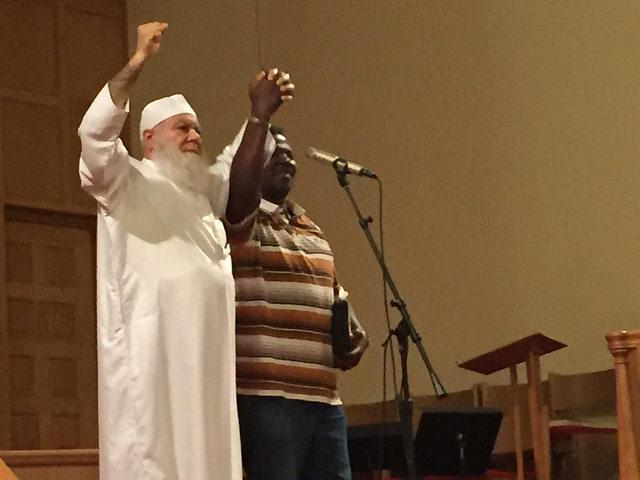 Two religious leaders hold hands on sanctuary