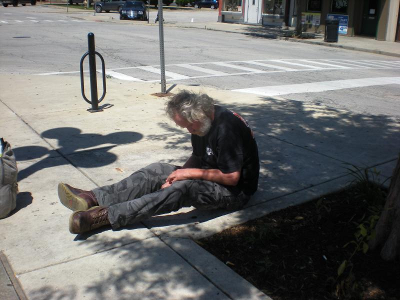 Todd Ledbetter, who frequented a city bench that was defaced, now sits on the ground where the bench once was located.