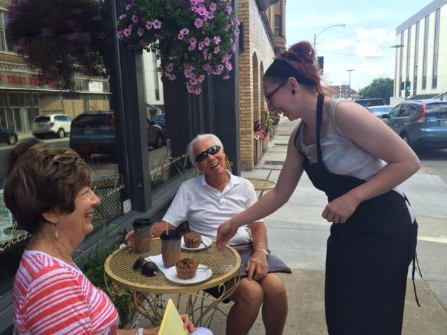 Server giving muffins to two people