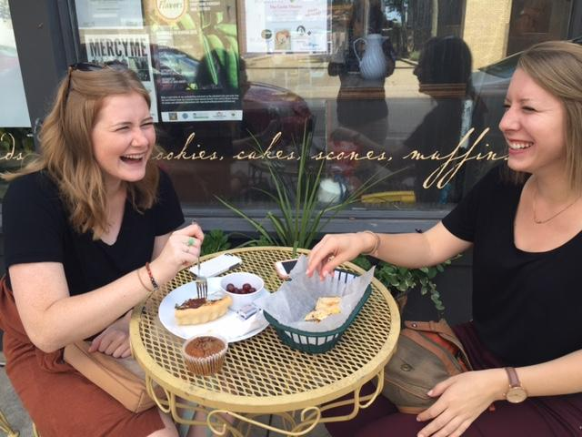 Two girls at outside table, laughing.