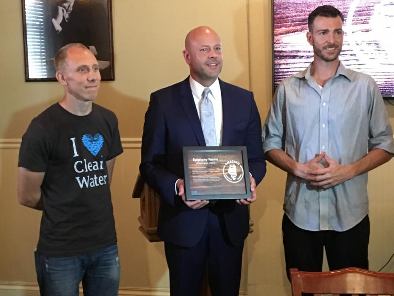 Illinois Office of Tourism Director Cory Jobe presents an Illinois Maker plaque to Ken Myszka and Stuart Hummel of Epiphany Farms