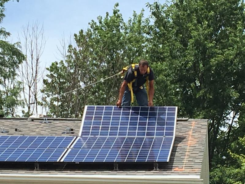 A installer from Wilcox Electric & Services, Inc. on the roof of the Packard's house