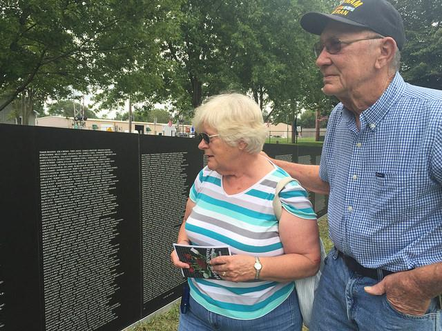 Couple looks at the American Veterans Tribute Wall at Evergreen Cemetery