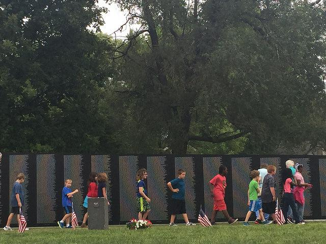Young children walk in front of the American Veterans Tribute Wall at Evergreen Cemetery in Bloomington.