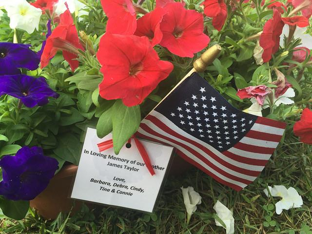 Flag, flowers and card with a tribute to a fallen Vietnam soldier at the American Veterans Traveling Tribute Wall at Evergreen Cemetery.