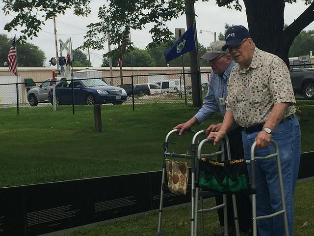 Two men with walkers visit the shorter end of the American Veterans Traveling Tribute Wall.