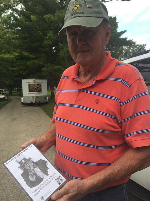 Veteran poses with a resource book at Evergreen Cemetery.