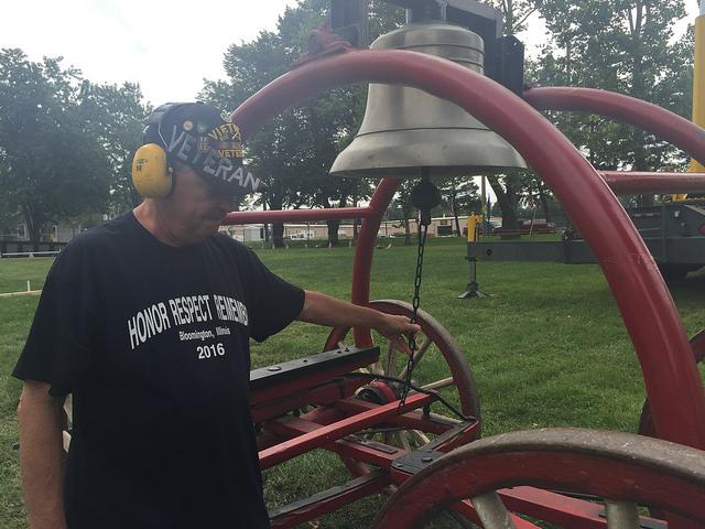 Guy ringing bell on the grouns of Evergreen Cemetery to announce the start of the display of the American Veterans Traveling Tribute Wall.