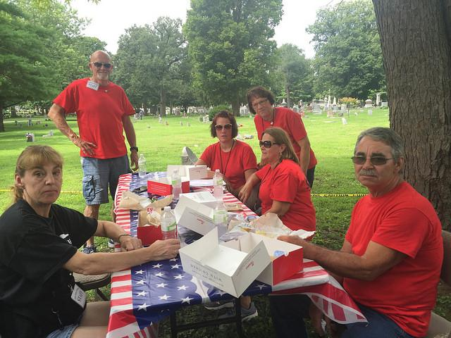 Crew pauses for lunch at the Traveling Tribute Wall at Evergreen Cemetery.