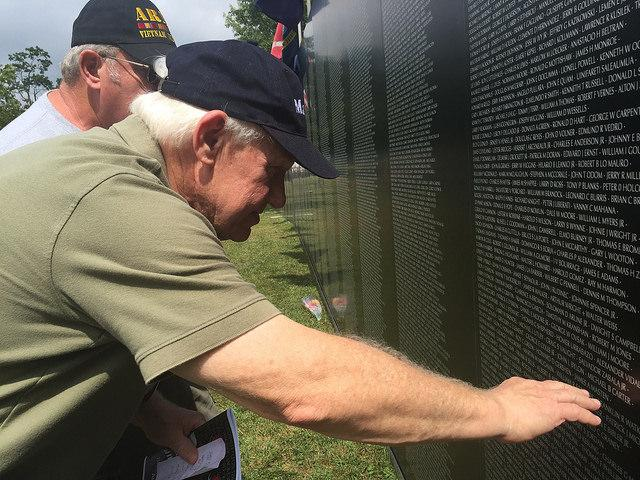 Two Vietnam Soldiers look at moving wall to find names of friends lost in the war.