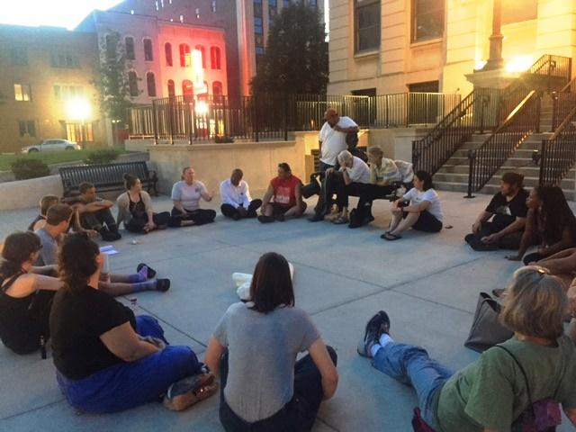 Group of 25 sits in a circle on the south side of downtown Bloomington courthouse.